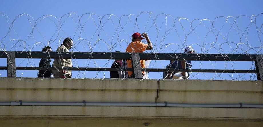 ARCHIVO— Personas deportadas caminan a lo largo del alambre de púas instalado en el Puente Internacional Juárez-Lincoln el viernes 16 de noviembre de 2018. Photo: Danny Zaragoza /Laredo Morning Times / Laredo Morning Times