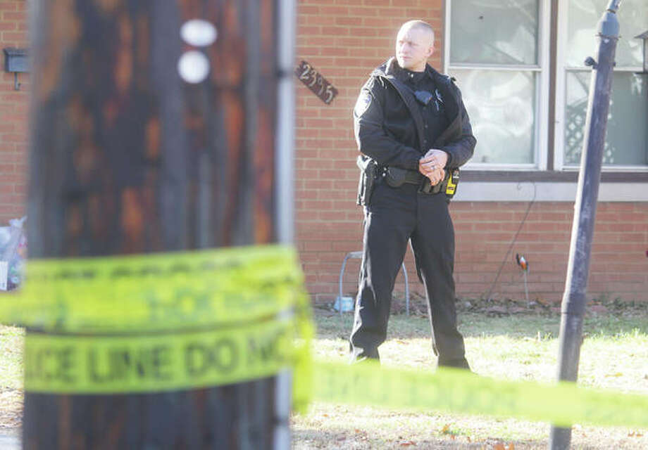 Alton Police Officer Nick Woelfel stands guard in front of a house in the 2300 block of Edwards Street after an early-morning double shooting Wednesday. Photo: Scott Cousins | The Telegraph