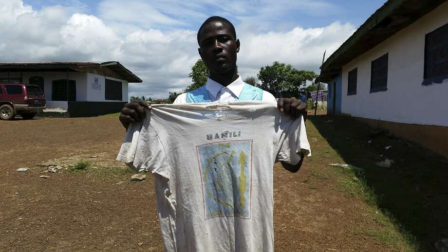 Moses Z. Kaine, 21, holds a T-shirt that his father, a West Africa peacekeeper, wore to visit his mother. Photo: Jonathan Paye-Layleh / Associated Press