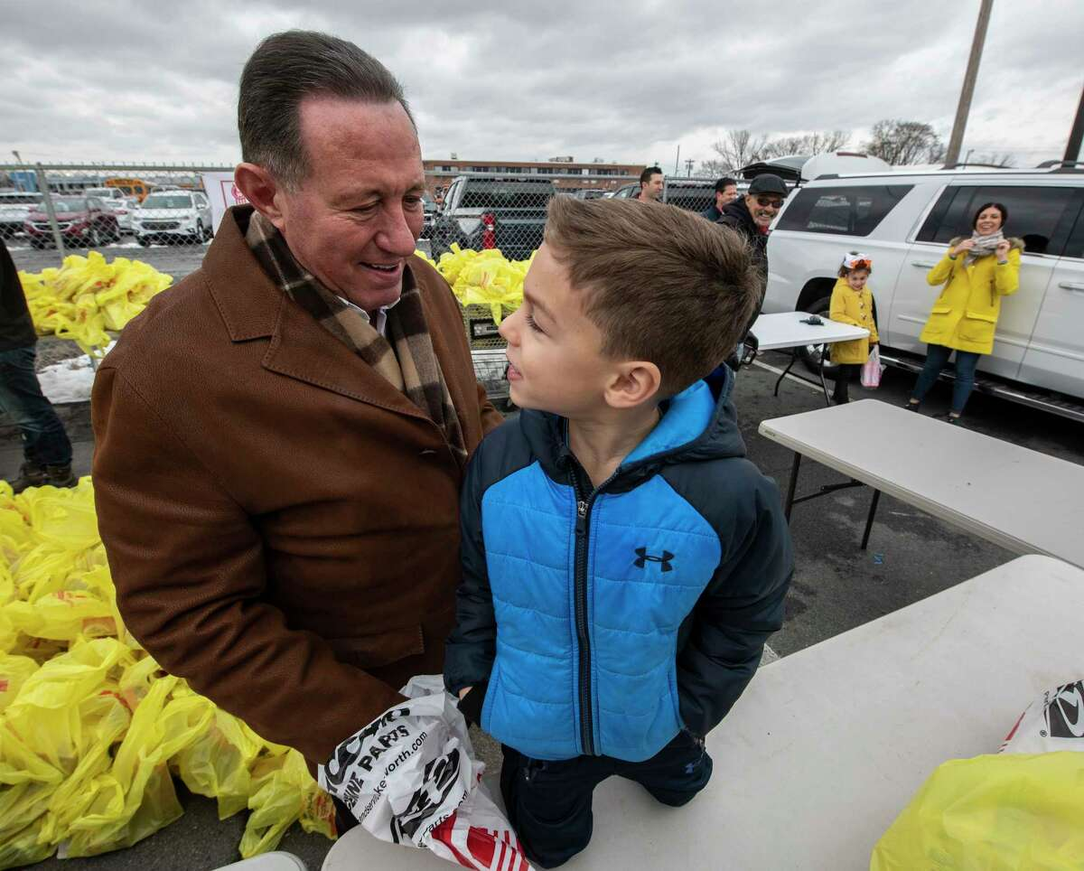 Local businessman Roddy Valente stands with his grandson Michael Redgrave, 5, who survived cancer and is the reason that Valente has donated turkeys that will be given to those in need outside the Capital OTB Wednesday Nov. 21, 2018 in Albany, N.Y. Also involved in the giveaway is Shoprite and Capital OTB. (Skip Dickstein/Times Union)