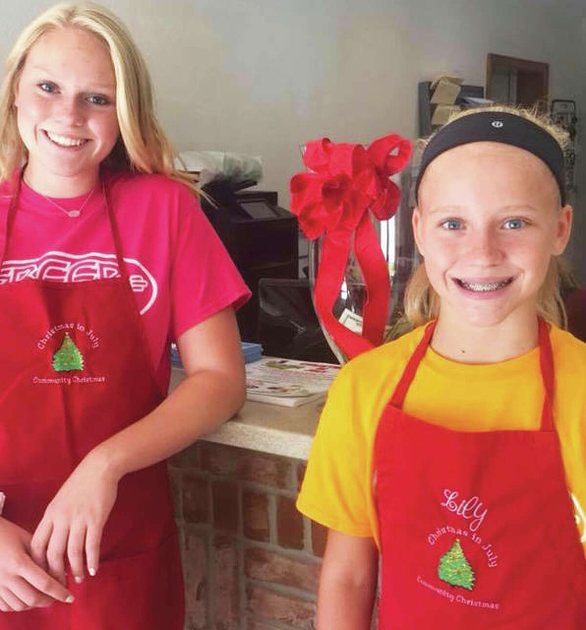 Taylor, left, and Lily Freer, right, help serve the holiday-decorated cookies and cocoa to guests at Freer Auto Body's annual Cookies and Cocoa Community Christmas event.