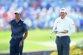 PONTE VEDRA BEACH, FL - MAY 11: Tiger Woods of the United States and Phil Mickelson of the United States stand on the 16th green during the second round of THE PLAYERS Championship on the Stadium Course at TPC Sawgrass on May 11, 2018 in Ponte Vedra Beach, Florida. (Photo by Sam Greenwood/Getty Images)