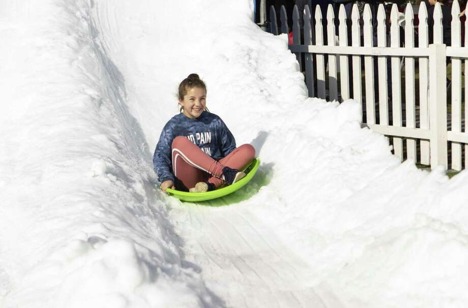 Emmylou Voelker, 10, rides down a snow slide at the 36th annual Lighting of the Doves Festival on Saturday, Nov. 17, 2018 at Town Green Park in The Woodlands. Photo: Cody Bahn, Houston Chronicle / Staff Photographer / © 2018 Houston Chronicle