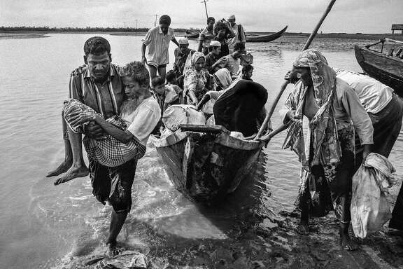A Bangladeshi boat driver carries Mohamed Halu, 70, to shore. Halu, who is blind, and his two daughters, fled their home in Maungdaw, Myanmar after an attack by Myanmar's military. Shah Porir Dwip, Bangladesh 2017.