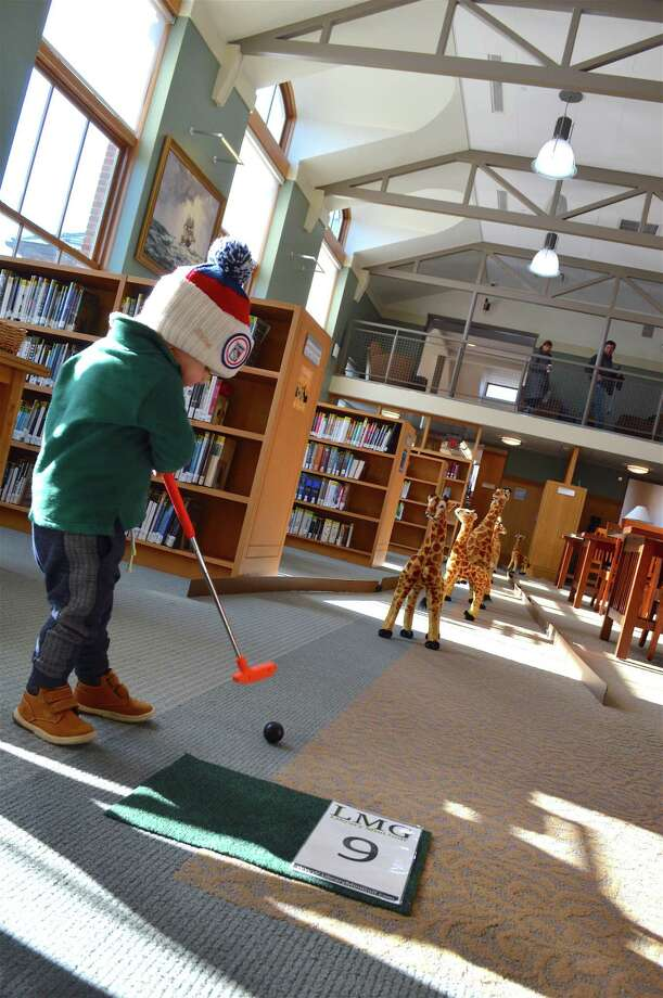 Gus Ceglarski, 21 months, of Darien tees off at the Darien Library's mini golf course, Saturday, Nov. 17, 2018, in Darien, Conn. Photo: Jarret Liotta / For Hearst Connecticut Media / Darien News Freelance