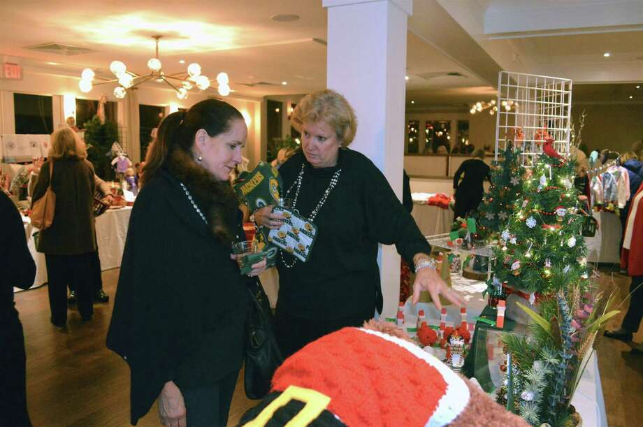 Lynn Carmichael, left, and Julie Williamson, both of New Canaan, discuss a purchase at the preview party for the New Canaan Artisans' annual Holiday Boutique, hosted at the Roger Sherman Inn in New Canaan on Nov. 16. Photo: Jarret Liotta / For Hearst Connecticut Media / New Canaan News Freelance