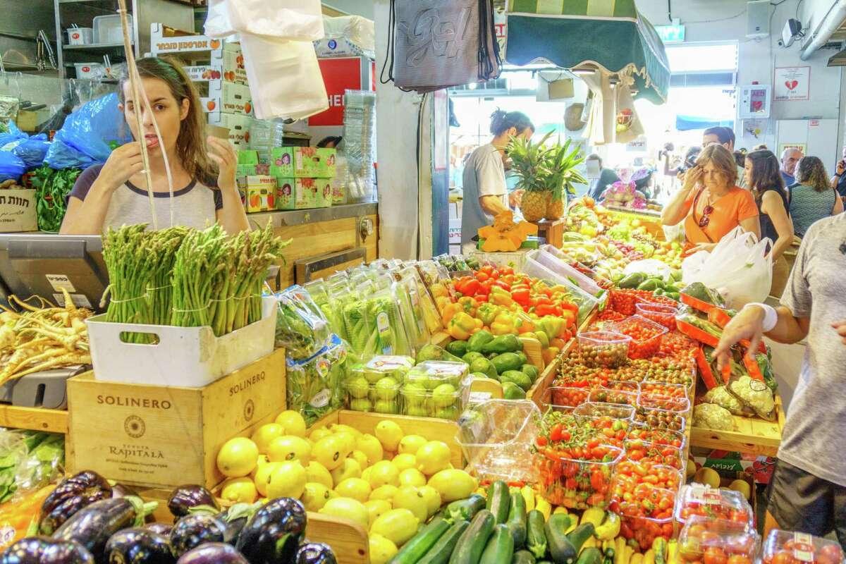 People shop at a fresh fruit stall in a Tel Aviv market.