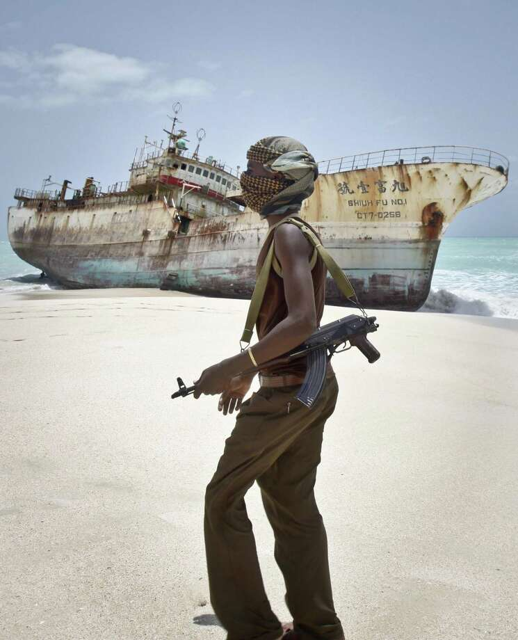 In this photo taken Sunday, Sept. 23, 2012, masked Somali pirate Abdi Ali walks past a Taiwanese fishing vessel that washed up on shore after the pirates were paid a ransom and released the crew, in the once-bustling pirate den of Hobyo, Somalia. Photo: Farah Abdi Warsameh, STR / Associated Press / AP
