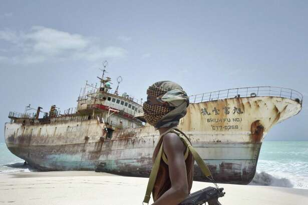 In this photo taken Sunday, Sept. 23, 2012, masked Somali pirate Abdi Ali walks past a Taiwanese fishing vessel that washed up on shore after the pirates were paid a ransom and released the crew, in the once-bustling pirate den of Hobyo, Somalia.