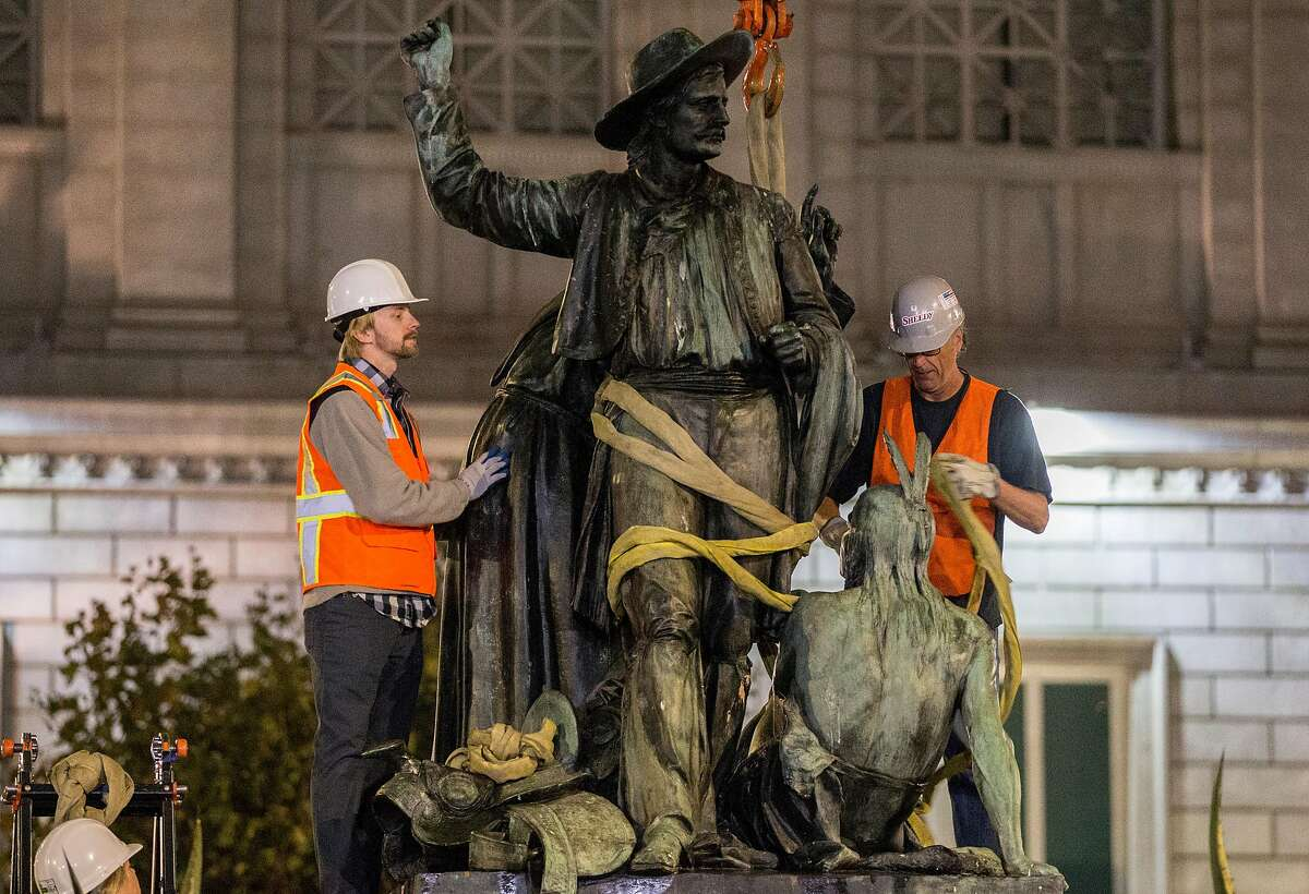 Workers remove the controversial 'Early Days' statue, one of five statues that make up the Pioneer Monument, at Civic Center Plaza in San Francisco Calif. Friday, Sept. 14, 2018.