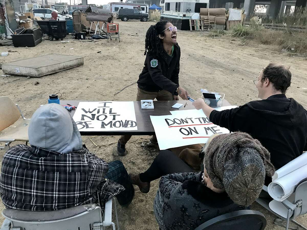Dayton Andrews laughs as Abraham Zamcheck hands him a marker. Andrews and Zamcheck are activists who were at the RV encampment on Wood Street in West Oakland on Sunday to help campers prepare to fight an eviction attempt by the property owner.