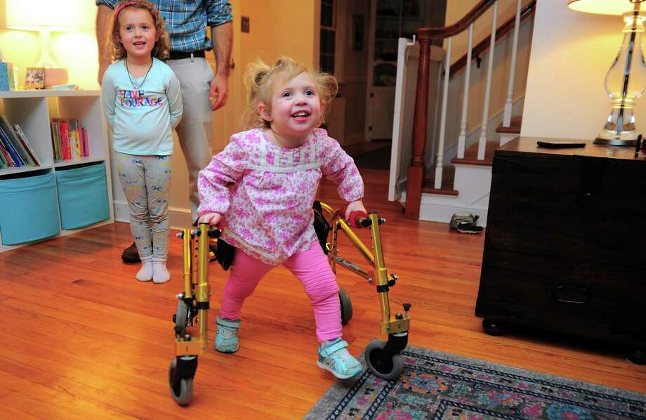 Serena Zitnay, 3, uses her walker to get around as her older sister Emma, 5, looks on at the family home in Orange. Photo: Christian Abraham / Hearst Connecticut Media / Connecticut Post