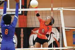 Edwardsville sophomore Alexa Harris, right, slams down a kill during a match against East St. Louis in the regular season.