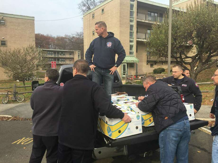 Members of the Greenwich Professional Firefighters union prepare to deliver boxes of food to residents of Armstrong Court on Monday. Photo: Jo Kroeker / Hearst Media Connecticut /
