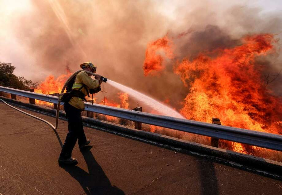 A firefighter battles a fire along the Ronald Reagan Freeway, aka state Highway 118, in Simi Valley, Calif., Monday, Nov. 12, 2018. (AP Photo/Ringo H.W. Chiu) Photo: Associated Press