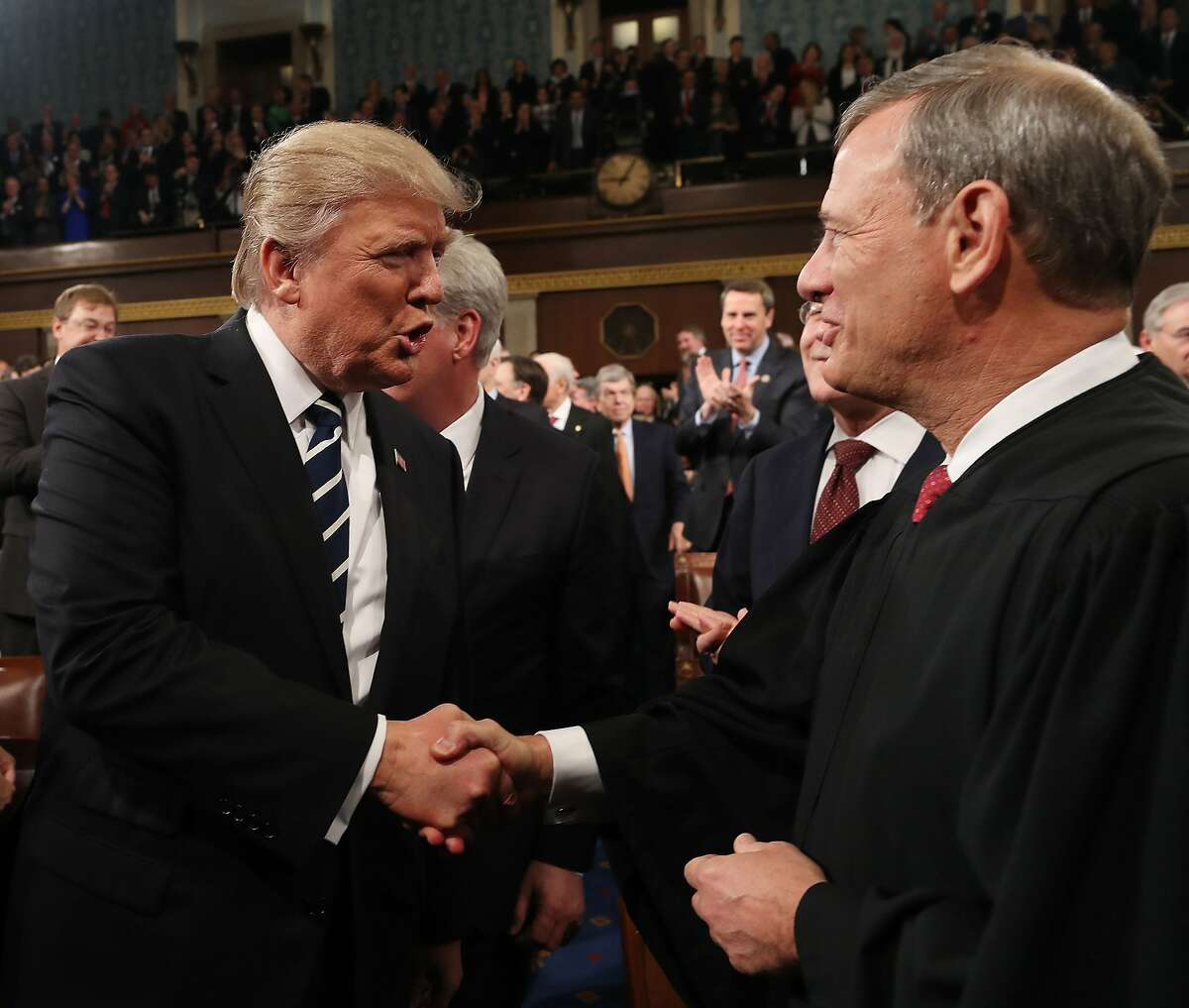 (FILES) In this file photo taken on February 28, 2017, US President Donald Trump (L) shakes hands with US Supreme Court Chief Justice John Roberts (R) as Trump arrives to deliver his first address to a joint session of Congress in Washington, DC.