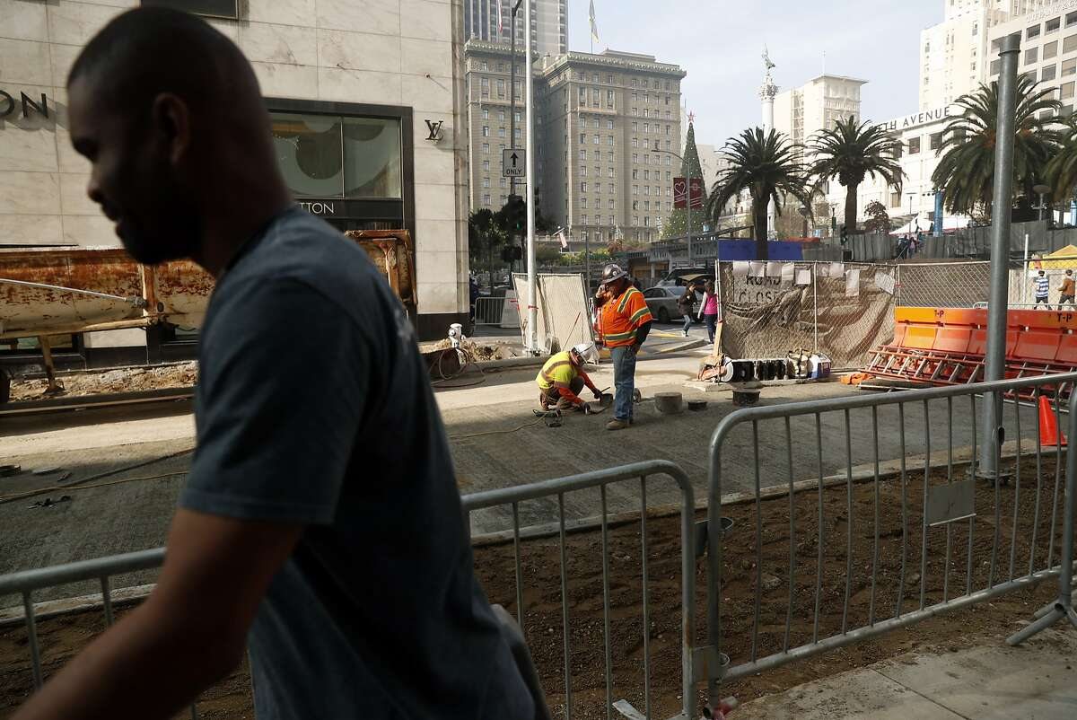Workers put the finishing touches on the Winter Walk and the Central Subway construction project on Stockton Street in San Francisco, Calif. on Monday, November 19, 2018.