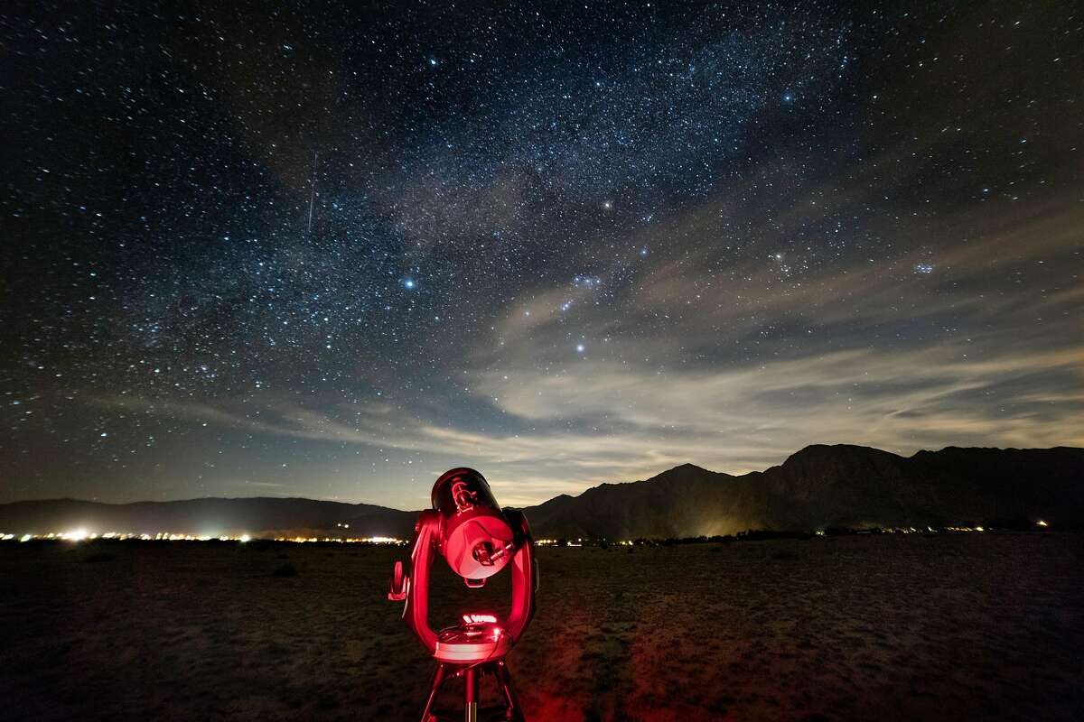 A telescope is illuminated red by an astronomer's flashlight under a starry desert sky near the village of Borrego Springs.