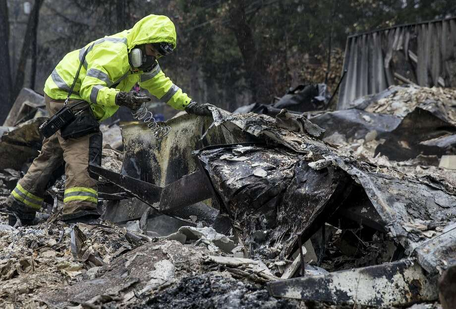 Search and rescue teams sift through the rubble for human remains as the rain falls along Pearson Road in Paradise, Calif. Wednesday, Nov. 21, 2018 after the Camp Fire devastated the entire town. Photo: Jessica Christian / The Chronicle