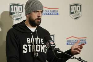 "Green Bay Packers quarterback Aaron Rodgers wears a sweatshirt that reads ""Butte Strong"" in support of the victims of the Camp Fire in Butte County, Calif., as he talks to reporters following the Packers' NFL football game against the Seattle Seahawks, Thursday, Nov. 15, 2018, in Seattle. The Seahawks won 27-24. (AP Photo/Stephen Brashear)"