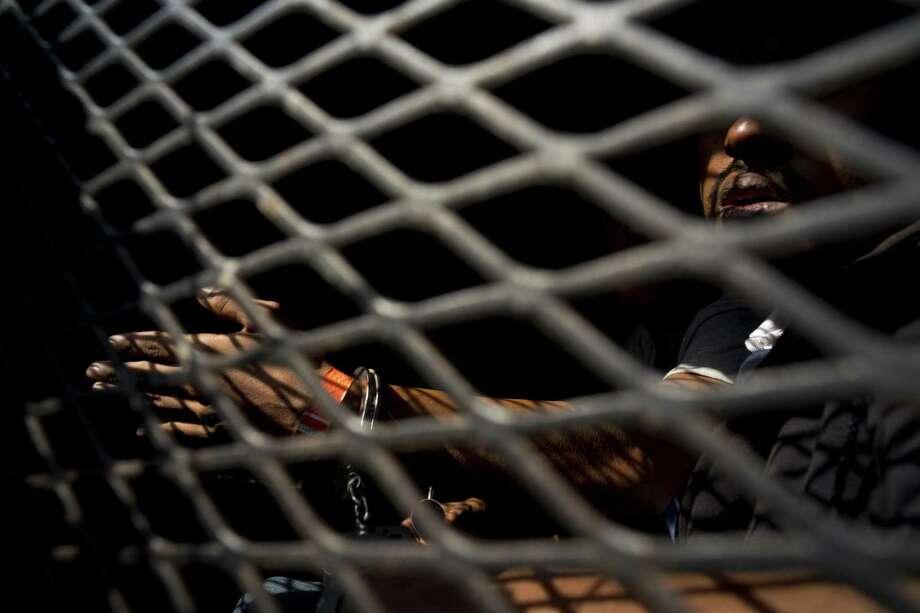 Un hombre que es parte de la caravana de migrantes centroamericanos, dentro de una camioneta de la policía después de ser arrestado, de acuerdo a las autoridades, por fumar marihuana, en Tijuana, México, el miércoles 21 de noviembre de 2018. Photo: Ramon Espinosa /Associated Press / Copyright 2018 The Associated Press. All rights reserved.
