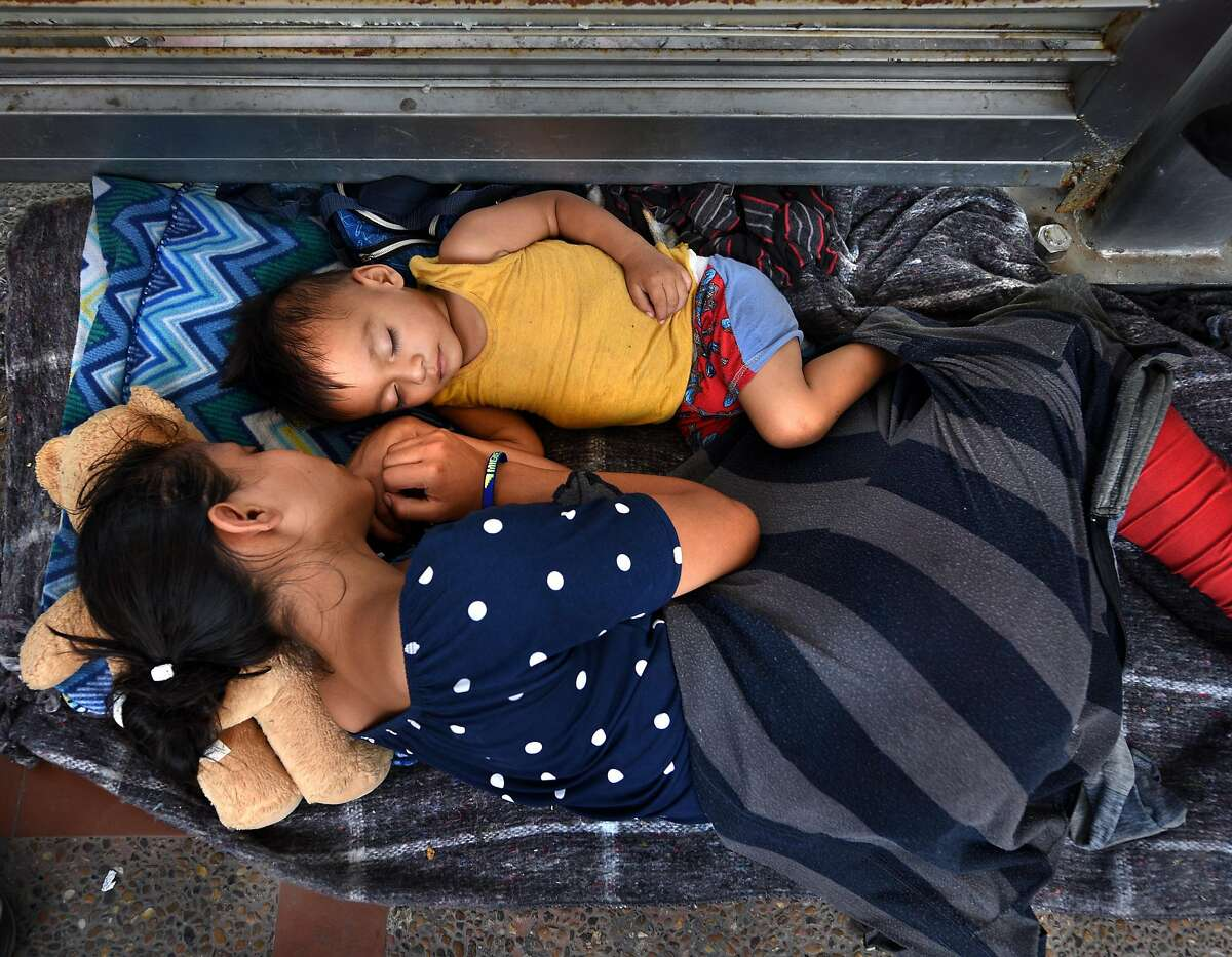 July 2, 2018 - Brownsville, Texas - Asylum seekers sleep on B/M Gateway bridge waiting to cross into U.S. from Mexico side. Ingrid Perdomo, 18 and her 1-year-old son Jose Luis take a nap in blistering heat. She came with her companion Luis Miguel, 32 from Honduras where they made the difficult 3 month journey. He said he fled in fear and cries a lot with anxiety about losing his past. His ex-wife started dating a gang member and the gang torched his home killing his 2 children inside. He fled to mountains seeking safety where he met Ingrid and they had another child. When they first arrived they said they were told by border guards they would not get in until their child was an adult, possibly as a deterrent then went to stay with a cousin in Mexico for a few days but had kidnap threats and returned to bridge July 1. They were eventually allowed in late on July 2 to be processed for credible fear. If not for a small humanitarian group Asociacion Civil Ayudandoles a Triunfar a.c. run by Glady Canas from Mexico they would have not had blankets to sleep on, food, water, etc. Carol Guzy/for San Antonio Express-News
