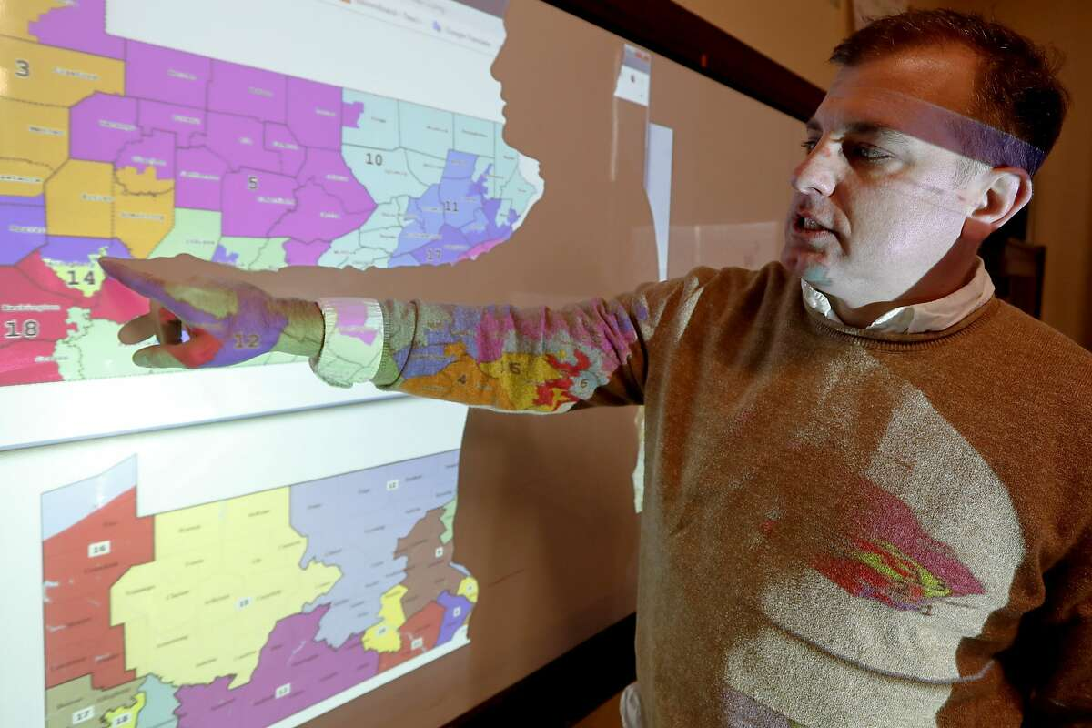 """William Marx, points to projected images of the old congressional districts of Pennsylvania on top, and the new re-drawn districts on the bottom, while standing in the classroom where he teaches civics in Pittsburgh on Friday, Nov. 16, 2018. Marx was a plaintiff in the Pennsylvania lawsuit that successfully challenged the Republican-drawn congressional maps. Marx said he believes the new district boundaries resulted in """"a more fair congressional representation of the will of the people in Pennsylvania."""" (AP Photo/Keith Srakocic)"""