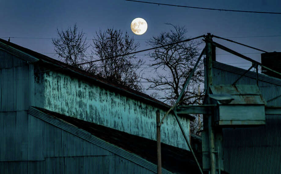 A 97-percent-full moon looms over the decaying 43,000-square-foot former Lenhardt Tool and Die property on Piasa St. in Alton Wednesday evening. The building is set to be razed early next year after being purchased by the city. Photo: Nathan Woodside | The Telegraph