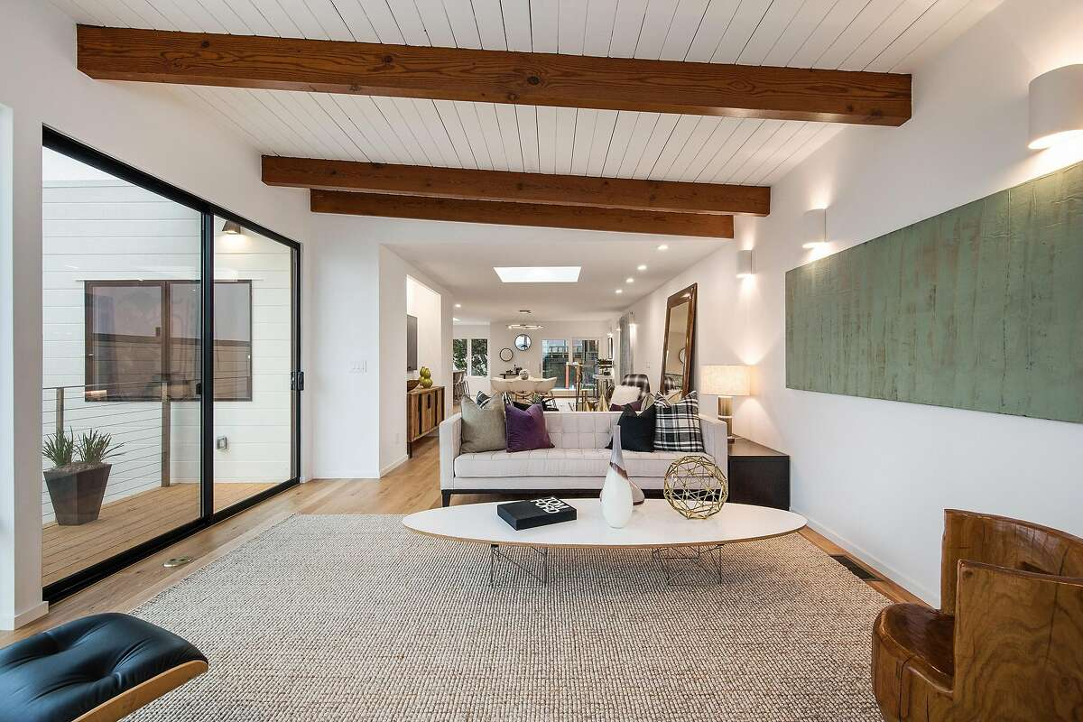 The main level features a flowing floor plan beneath a beamed ceiling punctuated by a skylight.