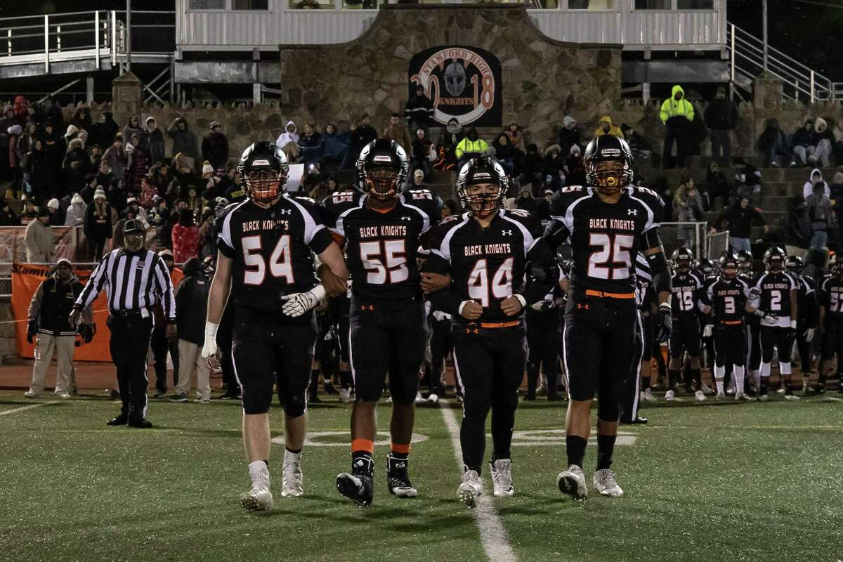 Stamford Black Knight Captains, David Marciczkiewicz (54), Manny Azolin (55), Michael Retana (44) and Austin Byrnes (25), lock arms and walk out to the coin toss, just prior to a Varsity High School Football game between the Stamford Black Knights and the Westhill Vikings, on November 21, 2018 at Boyle Stadium in Stamford, CT.