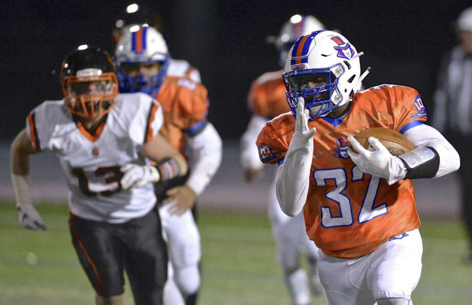 Danbury's Malik Thomas (32) broke a few tackles on his way to gaining 98 yards and scoring a touchdown against Ridgefield on Wednesday. Photo: H John Voorhees III / Hearst Connecticut Media / The News-Times