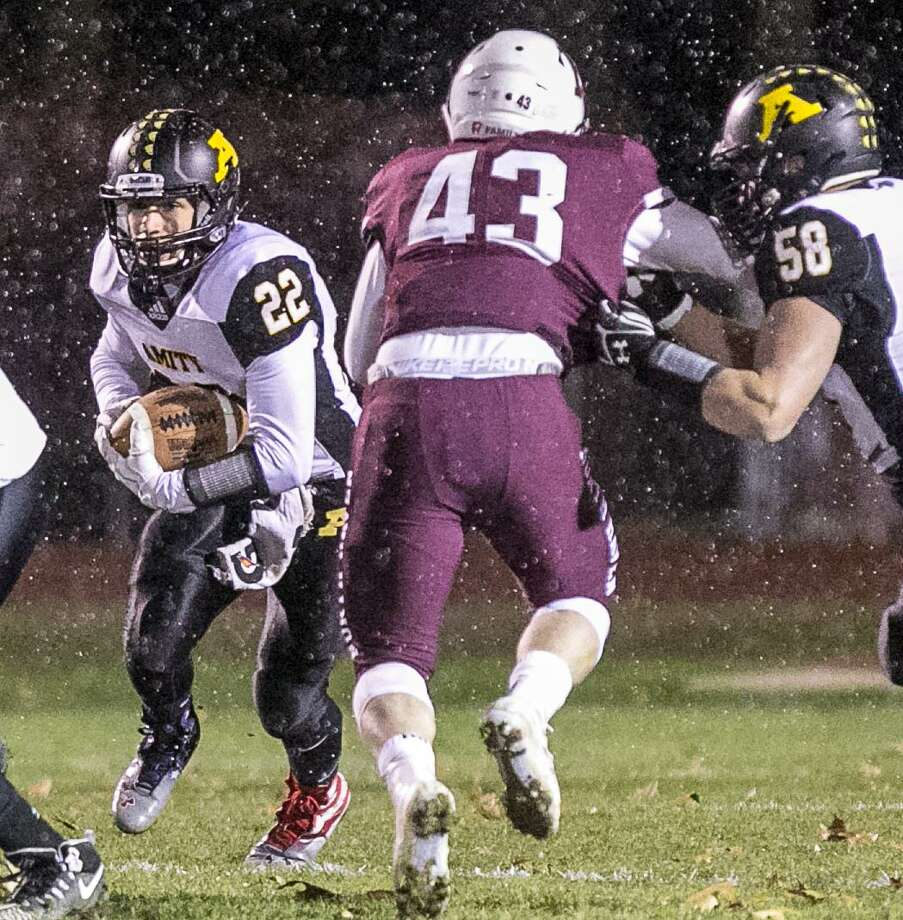 (John Vanacore For Hearst Connecticut Media) Amity's Michale Young looks to get past North Haven linebacker Vin DePalma during their annual Thankgiving game Wednesday evening. Photo: John Vanacore / For Hearst Connecticut Media / For Hearst Connecticut Media / (C)John H.Vanacore