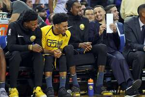 Golden State Warriors' Jordan Bell, Quinn Cook, Kevin Durant and Stephen Curry enjoy themselves in 2nd quarter against Oklahoma City Thunder during NBA game at Oracle Arena in Oakland, Calif. on Wednesday, November 21, 2018.