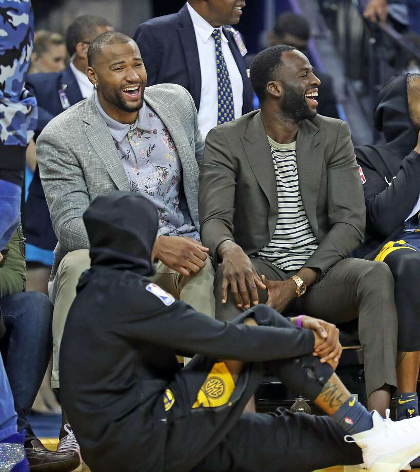 Golden State Warriors' DeMarcus Cousins and Draymond Green laugh while sitting on team bench in 1st quarter against Oklahoma City Thunder during NBA game at Oracle Arena in Oakland, Calif. on Wednesday, November 21, 2018. Photo: Scott Strazzante, The Chronicle
