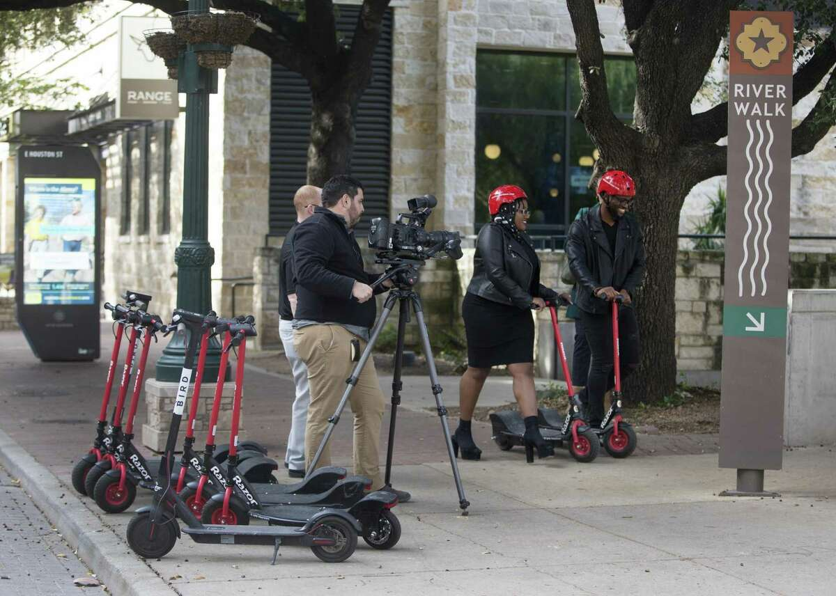Photographer Francisco Navarro, left, films actors Christian Reed-Ogba, center, and Uche Ogba Tuesday afternoon as they shoot a PSA for the city about e-scooter etiquette and rules.