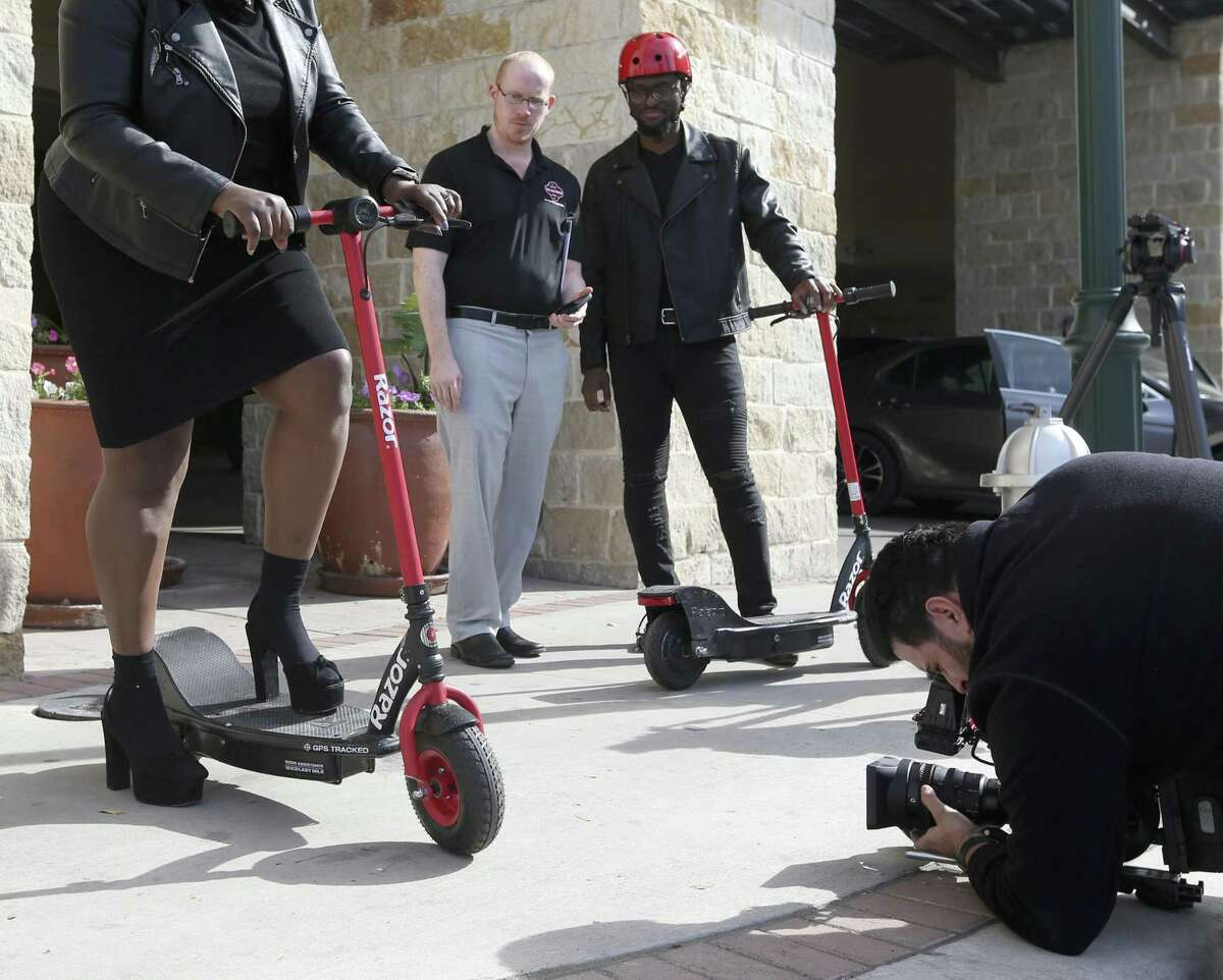 Photographer Francisco Navarro, right, films actor Christian Reed-Ogba as David McElroy, second from left, and Uche Ogba watch during the filming of a City of San Antonio sponsored-PSA about e-scooter etiquette and rules.