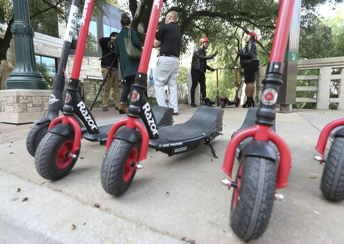 Actors Uche Ogba, second from right, and Christian Reed-Ogba, right, are filmed Tuesday afternoon, Nov. 20, 2018 in downtown San Antonio for a City of San Antonio sponsored-PSA about e-scooter etiquette and rules.