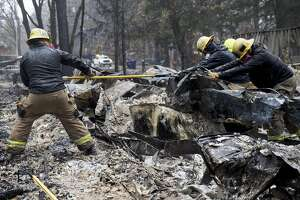 Search and rescue teams sift through the rubble for human remains as the rain falls along Pearson Road in Paradise, Calif. Wednesday, Nov. 21, 2018 after the Camp Fire devastated the entire town.