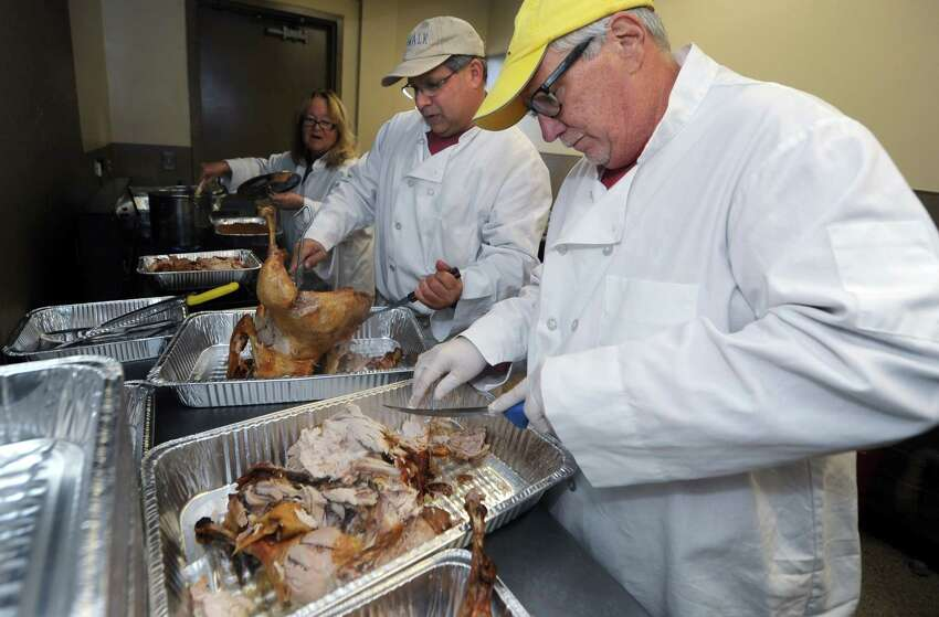 Volunteers Andy Garfunkel and Rick McQuaid carve the turkeys during The South Norwalk Community Association Thanksgiving Dinner Thursday, November 22, 2018, at the South Norwalk Norwalk Community Center in Norwalk, Conn. For more than two decades, Ernie Dumas and more recently the Association has been cooking up turkeys with a crew of volunteers to supply a Thanksgiving Day for the South Norwalk Community.
