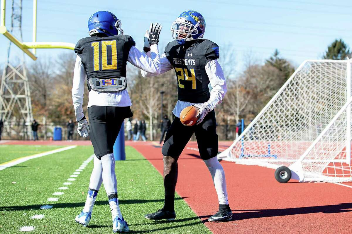 Isaiah Hanley (10), and Marcell Robinson (24), of Harding High School, celebrate a touchdown during a Varsity Football game between Bridgeport Central Hilltoppers and Harding Presidents on November 22, 2018 at Harding High School in Bridgeport, CT.