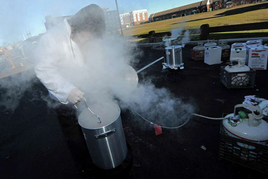Volunteer Peter Havens checks on the boiling turkeys during The South Norwalk Community Association Thanksgiving Dinner Thursday, November 22, 2018, at the South Norwalk Norwalk Community Center in Norwalk, Conn. For more than two decades, Ernie Dumas and more recently the Association has been cooking up turkeys with a crew of volunteers to supply a Thanksgiving Day for the South Norwalk Community. Photo: Erik Trautmann / Hearst Connecticut Media / Norwalk Hour