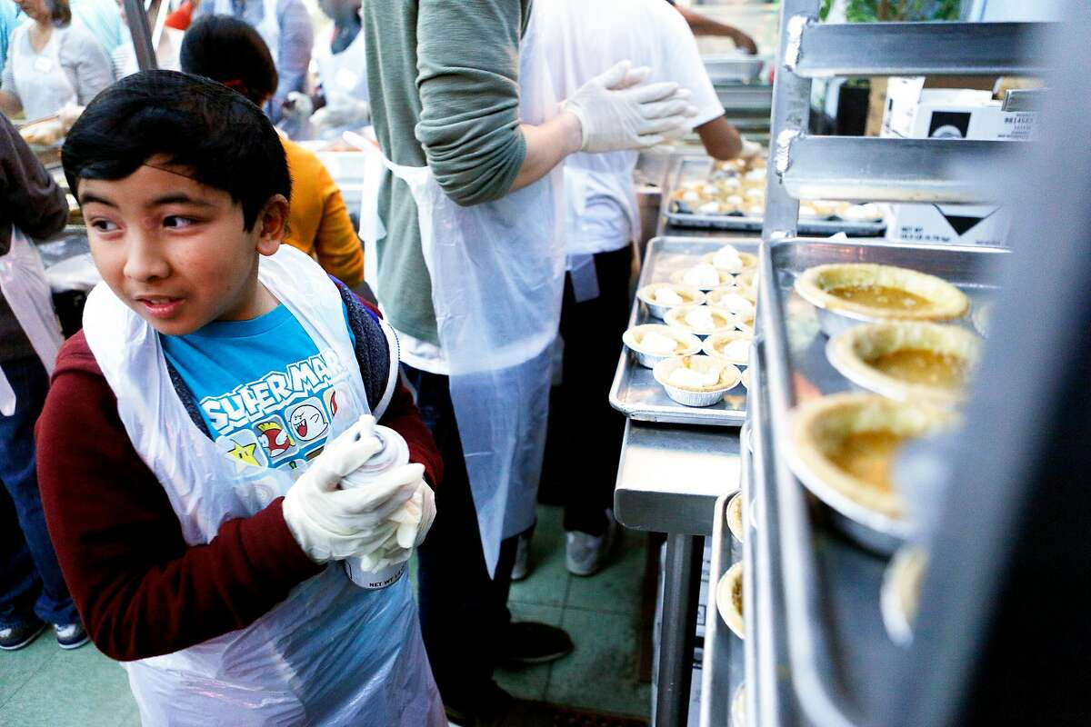 Deven Arcega, 11, fills the pies with whipped cream at Glide Memorial Church on Thursday, Nov. 22, 2018, in Oakland, Calif. Glide hosted a Thanksgiving meal for those in need.