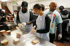 From left: Volunteers Lionel Stevens, Connie Rutherford, 14, and Jason Ross prepare sandwiches for those in need at Glide Memorial Church on Thursday, Nov. 22, 2018, in Oakland, Calif. Glide hosted a Thanksgiving meal for those in need.