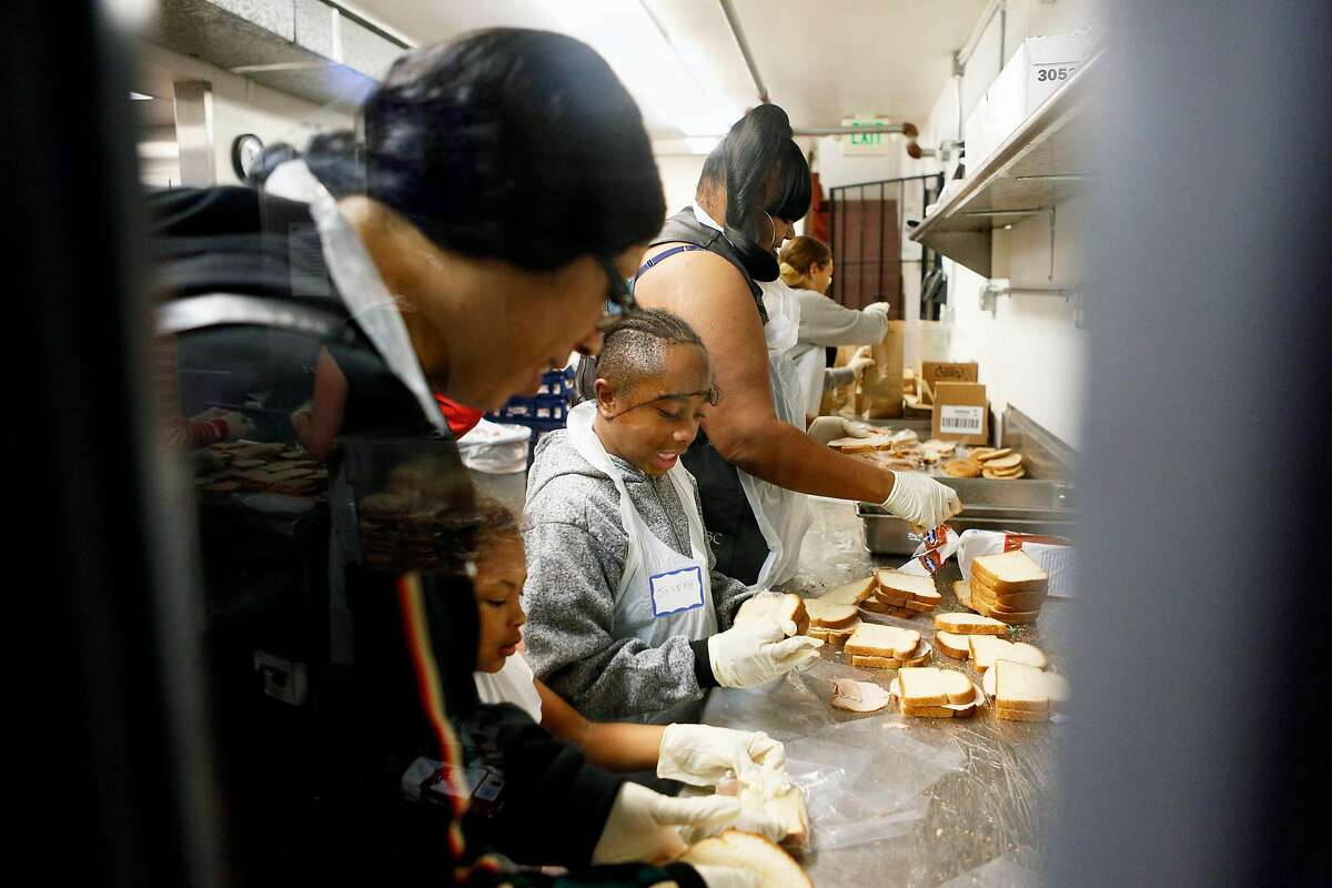 Josiah (center) and his family prepare sandwiches for people in need at Glide Memorial Church on Thursday, Nov. 22, 2018, in Oakland, Calif. Glide hosted a Thanksgiving meal for those in need.