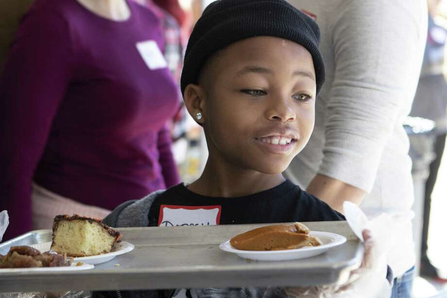 Volunteer Dorcell Hightower Jr., 8, passes out desserts Nov. 22, 2018 at the Salvation Army Wayne Bergstrom Center of Hope in Conroe. The Salvation Army and Friends of Conroe passed out Thanksgiving meals to those who needed them. Photo: Cody Bahn, Houston Chronicle / Staff Photographer / © 2018 Houston Chronicle