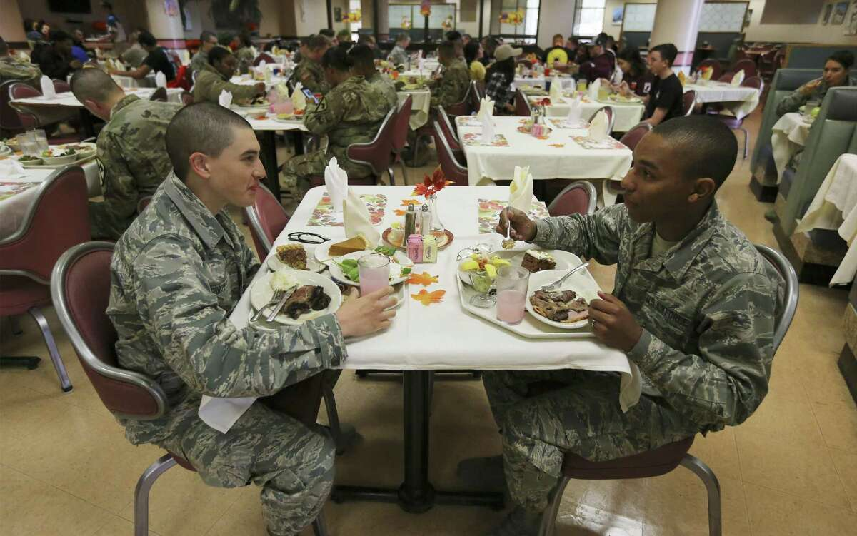 Airmen Andrew Cortez (left) and Devin Brown (right) sit down for a Thanksgiving meal at Joint Base San Antonio - Lackland on Thursday, Nov. 22, 2018. For many who are at Lackland's technical school and cannot go home for the holidays due to their training, higher ups served soldiers a Thanksgiving meal on base. A small group formed early before doors opened to Live Oak dining hall. And when 11 p.m. marked the commencement for the meal, a steady line of airmen filtered through the hall grabbing a tray and thinking about what they wanted for their Thanksgiving meal. Brig. Gen. Laura Lenderman, 502nd Air Base and JBSA Commander was on hand for a short time to personally serve plates of turkey, ham and roast beef along with all the trimmings. A sergeant could be heard urging the young airmen to consider the shrimp cocktail as an appetizer to the meal. Airmen gathered together at the tables to share the meal and to fellowship despite not being able to be home on this holiday. (Kin Man Hui/San Antonio Express-News)
