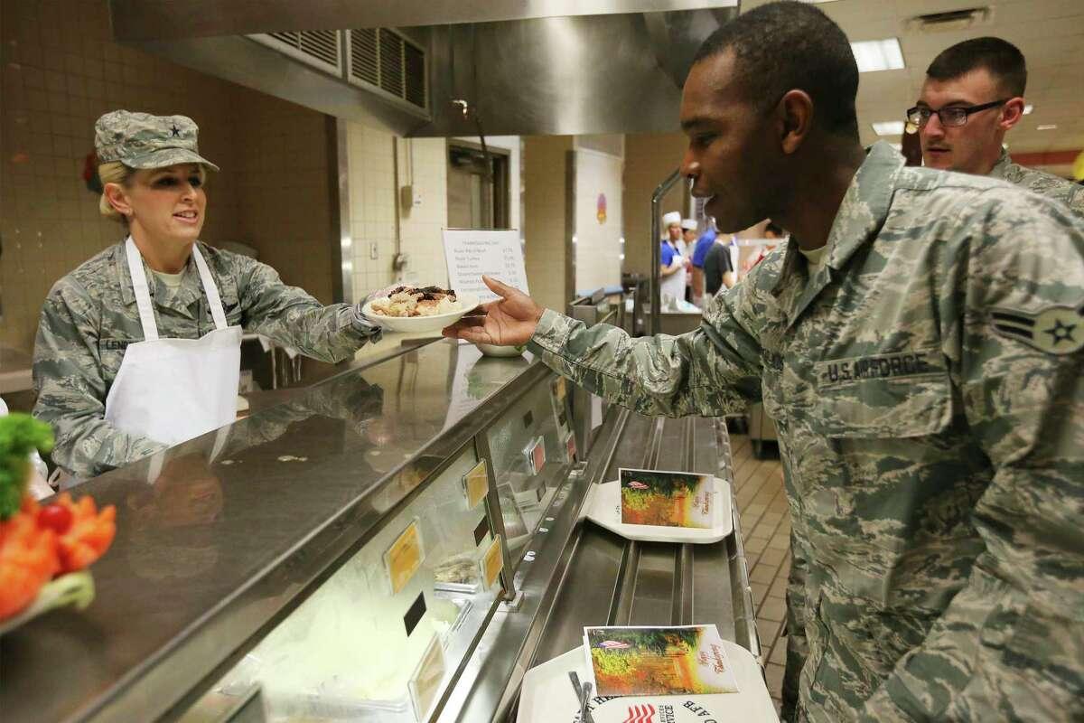 Brig. Gen. Laura Lenderman, JBSA Commander (left), hands a plate of food to Airman 1st Class Moutari Moussa as airmen enjoy a Thanksgiving meal at Joint Base San Antonio-Lackland in 2018. (Kin Man Hui/San Antonio Express-News)