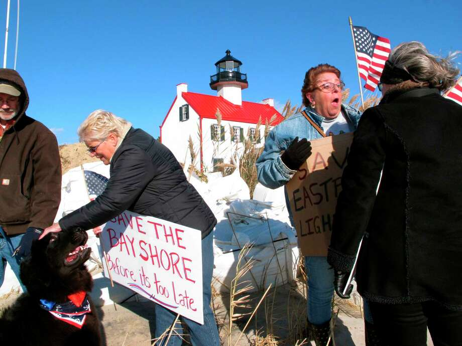 "In this Nov. 10, 2018, photo volunteers hold a ""Save The Lighthouse"" rally near the East Point Lighthouse in Maurice River Township, N.J. Rising seas and erosion are threatening lighthouses around the U.S. and the world, including the East Point Lighthouse. With even a moderate-term fix likely to cost $3 million or more, New Jersey officials are considering what to do to save the lighthouse. (AP Photo/Wayne Parry) Photo: Wayne Parry / Copyright 2018 The Associated Press. All rights reserved."