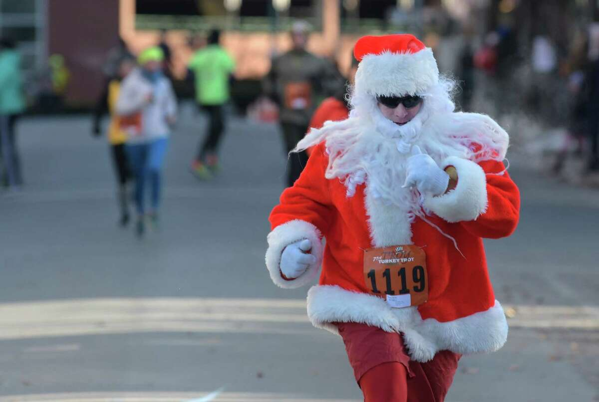 David Tromp, dressed as Santa, comes across the finish line in the 10K race at the Troy Turkey Trot on Thursday, Nov. 22, 2018, in Troy, N.Y. Tromp has run in the race since 1997. (Paul Buckowski/Times Union)