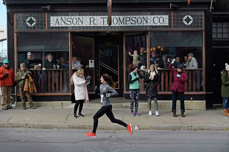 A runner in the 5K race makes her way past patrons of Anson R. Thompson Co., as they cheer her and other runners on at the Troy Turkey Trot on Thursday, Nov. 22, 2018, in Troy, N.Y. Click through the slideshow to see more of Paul Buckowski's most notable photographs from 2018. Photo: Paul Buckowski / (Paul Buckowski/Times Union)